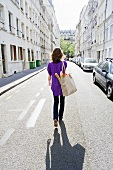 Woman Walking down the Street in Paris France with a Cloth Bag; Baguette and Flowers