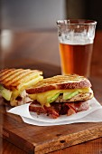 Chicken, avocado and bacon panini with a glass of beer