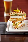 Chicken and avocado panini held together with a toothpick and garnished with pepperoncini and a glass of beer
