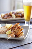 Grilled shrimp kebabs with lemon wedges and bread and a glass of beer