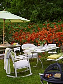 An afternoon barbeque in a garden with a red flower bed in the background