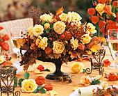 Herbstliches Gesteck aus Rosen und Hagebutten
