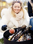 Frau grillt Apfel im Winter