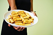 A woman holding a plate of spring rolls