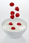Raspberries falling into a bowl of yogurt