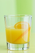 A glass of orange juice with orange slices