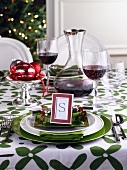A table laid in green and white for Christmas with red wine