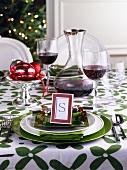 Grün-weiss gedeckter Weihnachtstisch mit Rotwein