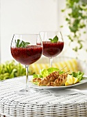 Chicken Satay and berry ice cream with mint in stemware glasses