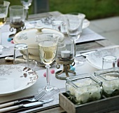 A table laid with glasses of wine and flowers in glass containers