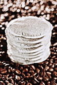 A stack of coffee pads on coffee beans