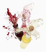 Wine spraying out of bottles (red wine, rose wine and white wine)