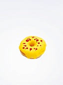 A doughnut with yellow icing and red dots