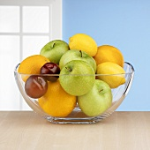 Fresh fruit in glass bowl in front of window