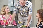 Mann serviert zwei Frauen Salatteller