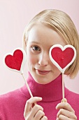 Young woman with heart-shaped lollipops in front of her eyes