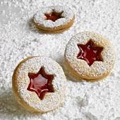Three Linzer biscuits on icing sugar