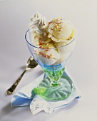 Vanilla ice cream with cream & sprinkles in a sundae glass