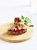 A slice of wholemeal bread with tomatoes and ham