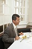 Mann sitzt im Restaurant vor einem Salatteller