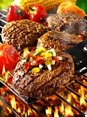 Burgers with vegetables on barbecue rack and spatula
