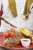 Woman eating T-bone steak with accompaniments