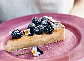 A piece of blackberry tart with pansies