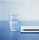 A glass of mineral water beside a notebook and pencil