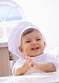 Little girl in chef's hat with floury hands