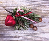 Pine sprig with Christmas decoration on a wooden surface