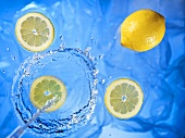 Stream of water running onto lemons and lemon slices