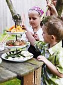 Children at smorgasbord in garden (Sweden)