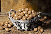 Unshelled macadamia nuts in and beside a wicker basket