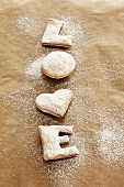 Freshly baked 'LOVE' biscuits with icing sugar