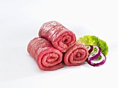 Raw beef for roulades with onion rings and lettuce leaf