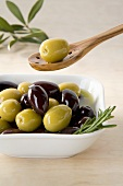 Green and black olives in small dish and on wooden spoon
