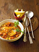 Fish curry with tomatoes and ginger in a white bowl