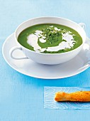 Pea soup with chives, horseradish cream and a puff pastry stick