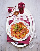 Fine fish carpaccio with sesame seeds on a table decorated for Christmas
