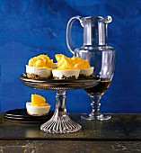 Mini lemon cheesecakes on a cake stand against a blue background