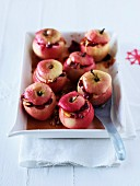 Baked apples with white chocolate sauce, cranberries and almonds