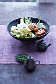 Pork fillet with spring vegetables in a black bowl