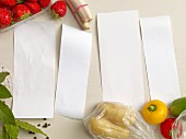 Four blank pieces of paper surrounded by fruit, vegetables and spices