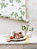 Vanilla and strawberry parfait on the table against a wall decorated with various roles of wallpaper