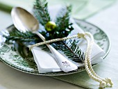 A napkin and a pine sprig on a plate decorated for Christmas