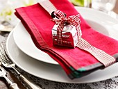 A place setting decorated with a red napkin and tiny present