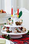 Wooden angels, berries, nuts and candles on a stand for Christmas