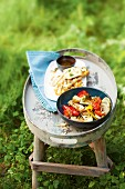 Oven-roasted vegetables and grilled halloumi on a table outside