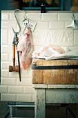 A leg of pork on a hook and a goose on a wooden board in a butcher's shop