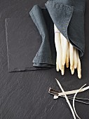 White asparagus spears with cloth napkins and a peeler on a black surface